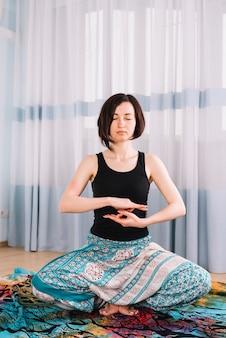 Het portret van een mooie jonge vrouwenzitting in yoga stelt