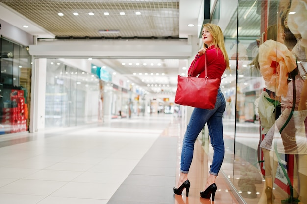 Het portret van een mooie vrouw die rode blouse, toevallige jeans en zwarte hoge hielen draagt stelt met rode leerhandtas in reusachtig winkelcomplex.