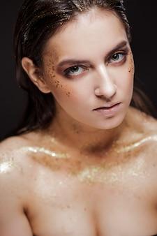 Het portret van een mooie vrouw met creatief goud maakt omhoog