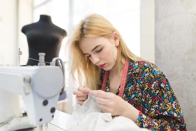 Het portret van een naaister zit op de werkplek bij een naaimachine