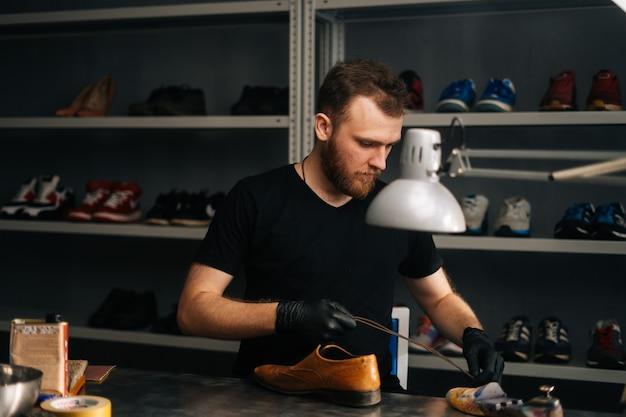 Het portret van een schoenmaker die zwarte handschoenen draagt, steekt een klompblok in versleten lichtbruine leren schoenen