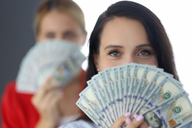 Het portret van een succesvolle onderneemster die amerikaanse dollars in handen houdt voor haar gezicht. teamwork winst concept.
