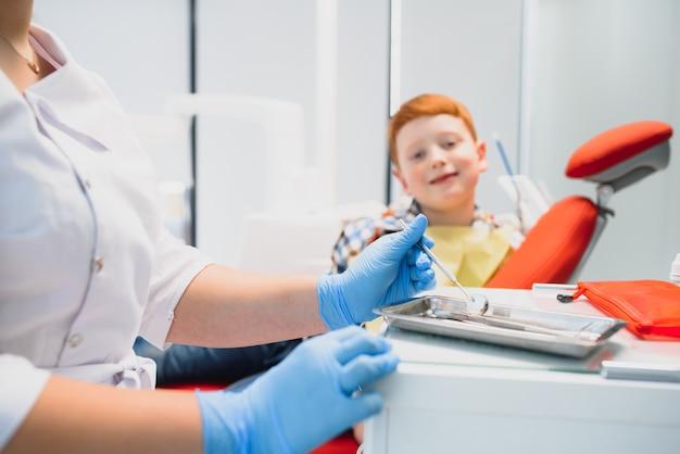 Het portret van een tandarts die tandheelkundige instrumenten in zijn handen houdt in de kliniekclose-up