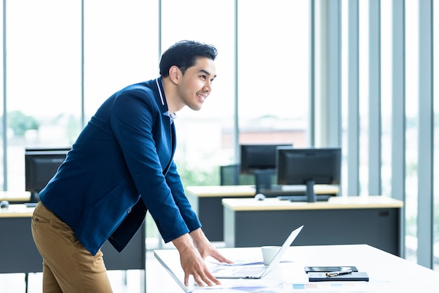 Het portret van een vrolijke rijpe aziatische jonge zakenman draagt een pak van de mens in blauw overhemd en laptop die het venster in de bureauruimte bekijken.