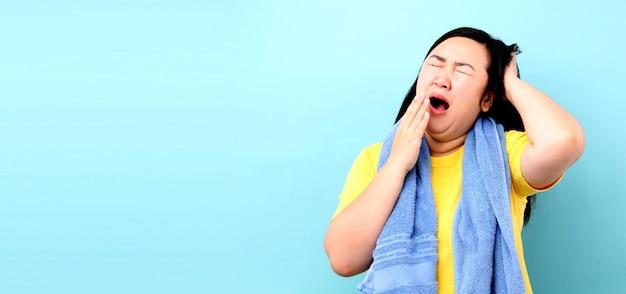 Het portret van een vrouw van azië voelt slaperig, terwijl het lopen om op blauwe achtergrond in studio te douchen