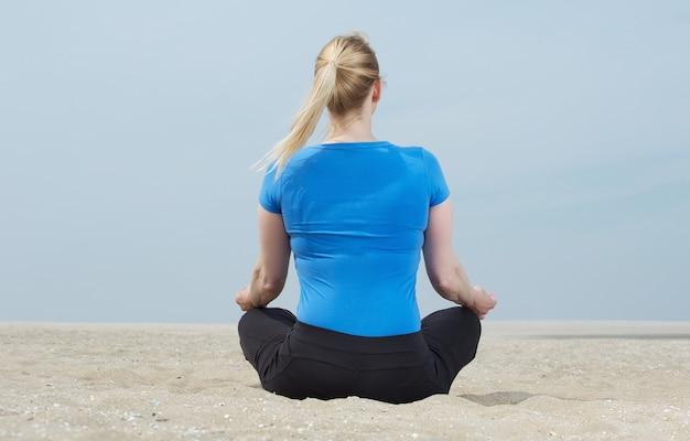 Het portret van een vrouwenzitting op zand in yoga stelt