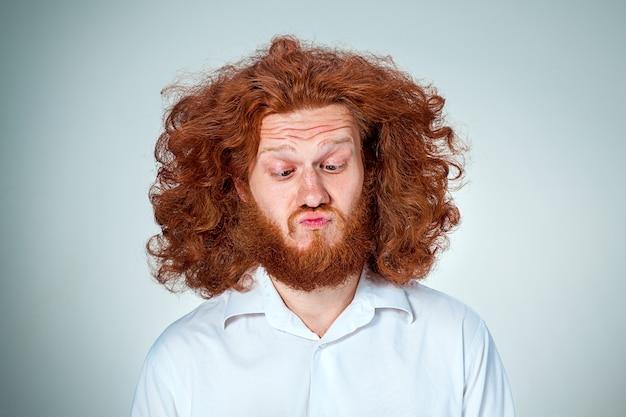 Het portret van een weerzinwekkende man met lang rood haar