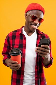 Het portret van een zwarte amerikaanse mens kleedde stylishly houdend een drankglas op koffiepauze met gele telefoon