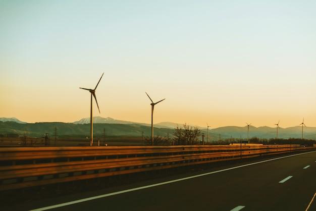 Het portret van eolian-energie, gaat groen, windturbines langs de weg bij zonsondergang
