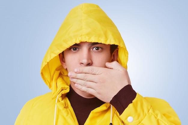 Het portret van ernstige aantrekkelijke modieuze kerel behandelt mond met handen, probeert om het geheim van de vriend niet te vertellen, privé informatie vertrouwelijk te houden