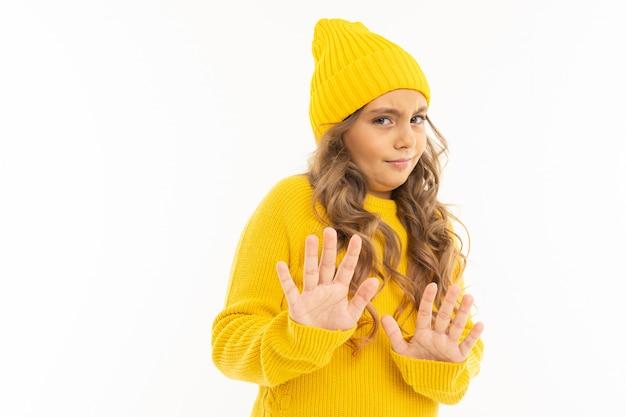 Het portret van europees aantrekkelijk meisje in een gele hoed toont ontevredenheid met handen op een wit met copyspace