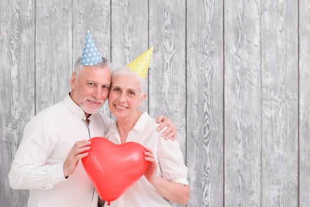 Het portret van gelukkig hoger paar die verjaardagshoed dragen die rood houden hoort vormballon vooraan houten achtergrond