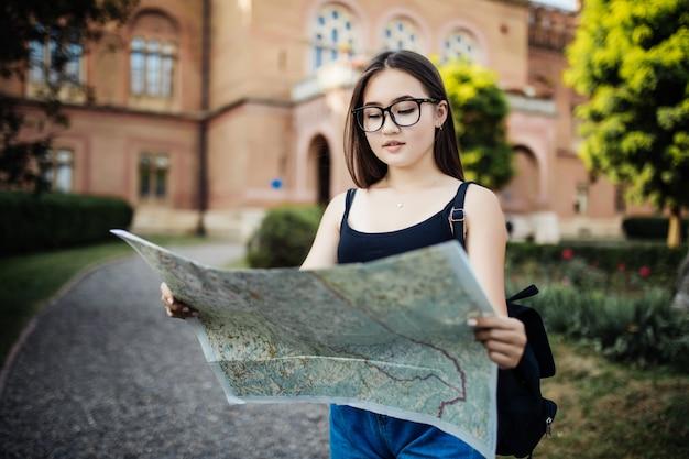 Het portret van gelukkig jong meisje brengt rugzak zoekend iets en houdt kaartreis in onbekende stad