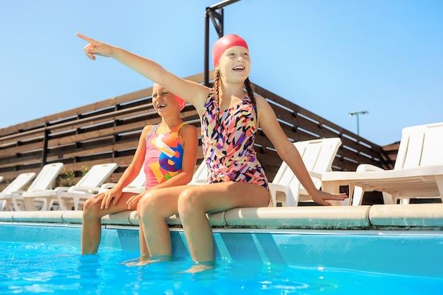 Het portret van gelukkig lachend mooie tienermeisjes bij het zwembad