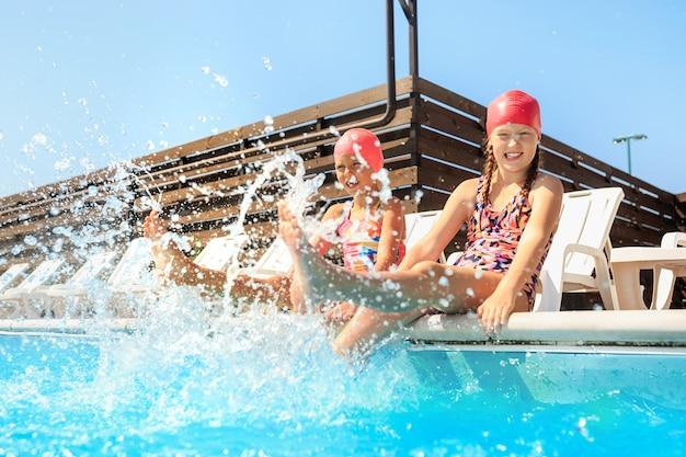 Het portret van gelukkig lachend mooie tienermeisjes bij het zwembad.