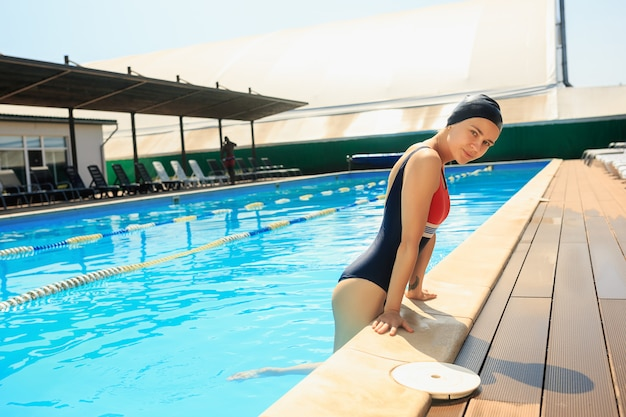 Het portret van gelukkig lachend mooie vrouw bij het zwembad