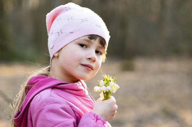 Het portret van gelukkige de holdingsbos van het kindmeisje van vroege de lentesneeuwklokjes bloeit in openlucht.