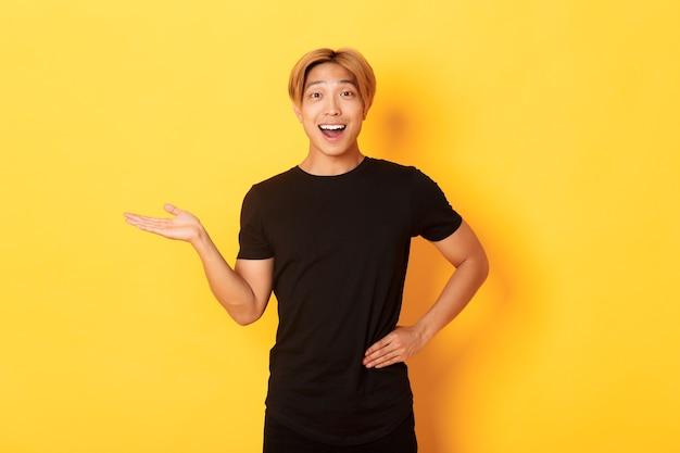 Het portret van gelukkige en opgewekte glimlachende aziatische kerel die iets op hand overhandigt gele muur