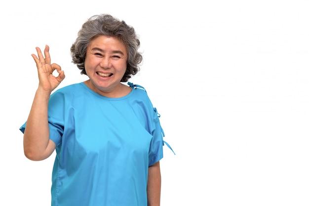 Het portret van gelukkige hogere aziatische vrouwenpatiënt die hand ok tonen en camera bekijken die op witte muur wordt geïsoleerd, ouder wijfje die positief voelen en geniet van concept