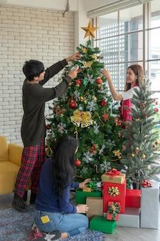 Het portret van gelukkige jonge aziatische dame verfraait kerstboom met haar vrienden, kerstmistijd, vakantie