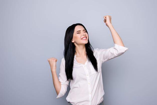 Het portret van gelukkige leuke jonge vrouw met brede glimlach stak handen op en viert prestatiedoel