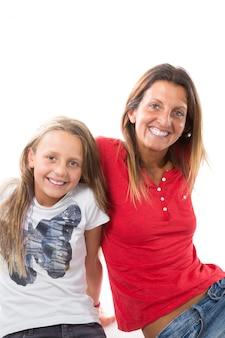 Het portret van gelukkige moeder en dochter zit op het schot van de vloerstudio dat op witte achtergrond wordt geïsoleerd