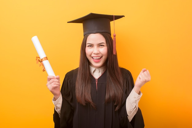 Het portret van gelukkige mooie vrouw in graduatietoga houdt onderwijscertificaat op gele achtergrond