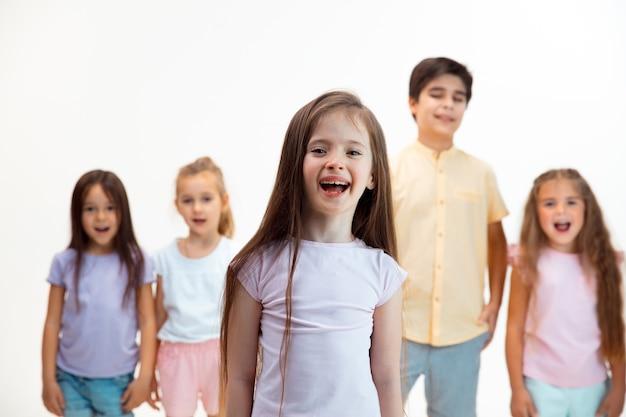 Het portret van gelukkige schattige kleine kinderen jongen en meisjes in stijlvolle vrijetijdskleding camera kijken tegen witte muur