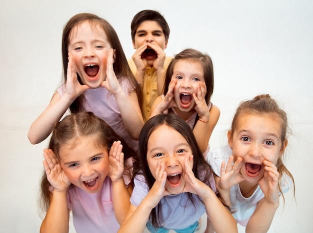 Het portret van gelukkige schattige kleine kinderen jongen en meisjes in stijlvolle vrijetijdskleding voorzijde tegen witte studiomuur kijken