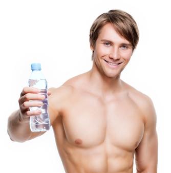 Het portret van gelukkige spier shirtless sportman houdt water - dat op witte muur wordt geïsoleerd.