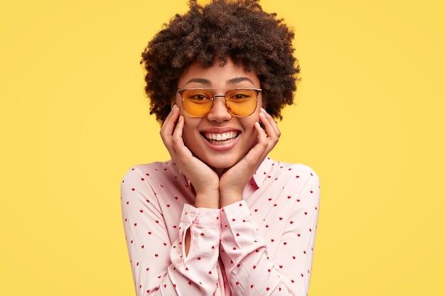 Het portret van gelukkige zwarte jonge vrouw heeft prettige brede tedere glimlach, houdt kin