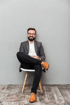 Het portret van gemiddelde lengte van de ontspannen mens in toevallige zitting op stoel in bureau en het glimlachen op camera, dat over grijs wordt geïsoleerd