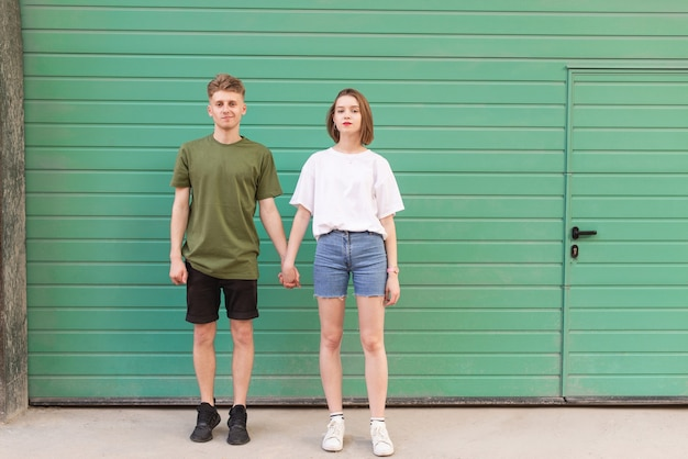 Het portret van gemiddelde lengte van een jongen en meisjesholdingshanden en status op green
