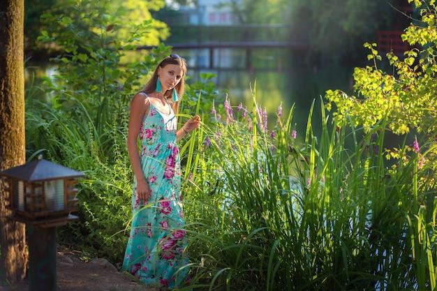 Het portret van gemiddelde lengte van een mooi meisje dichtbij een meer met lang gras. zomer wandeling. lange vloer vlate