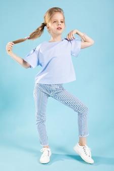 Het portret van gemiddelde lengte van een mooi meisje in blauwe kleren op een blauw.
