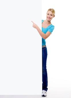 Het portret van gemiddelde lengte van een mooie blonde vrouwelijke persoon wijst op het lege aanplakbord - dat op wit wordt geïsoleerd