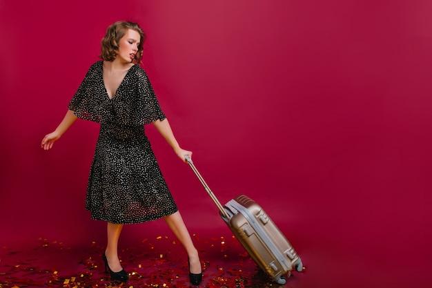 Het portret van gemiddelde lengte van elegant vrouwelijk model in de lange koffer van de kledingsholding vóór reis
