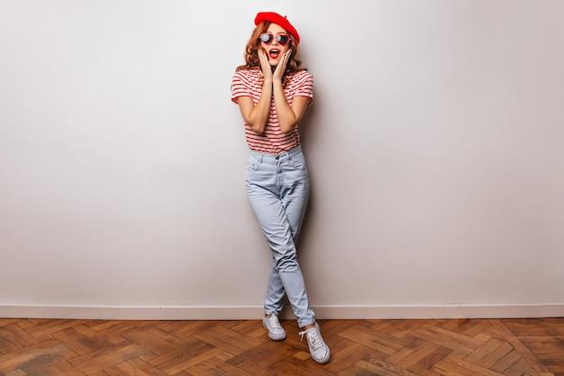 Het portret van gemiddelde lengte van goedgehumeurd meisje in franse baret. prachtig europees model in spijkerbroek lachend op een witte muur.