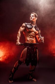 Het portret van gemiddelde lengte van het sexy jonge zwaard van de strijdersholding en weg het kijken terwijl het stellen tegen brand.
