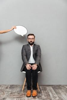 Het portret van gemiddelde lengte van jonge mensenzitting op stoel die handen op knieën met lege toespraakbel neerzetten boven zijn hoofd, dat over grijs wordt geïsoleerd