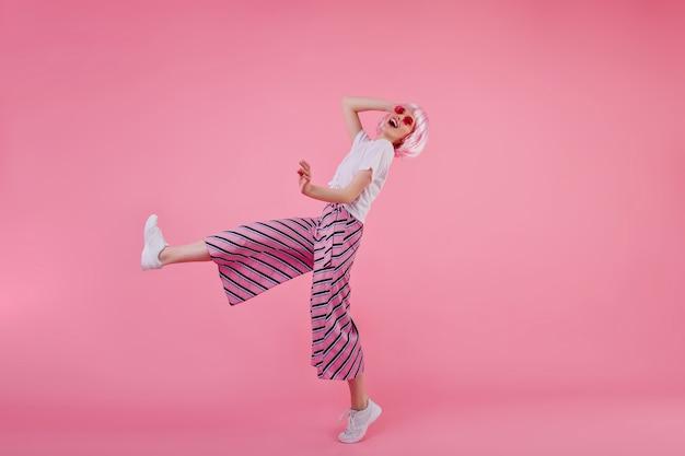 Het portret van gemiddelde lengte van jonge vrouw in trendy broek die met gelukkige glimlach dansen. binnen schot van slank stijlvol meisje in roze pruik met plezier