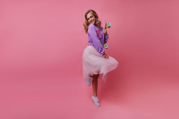 Het portret van gemiddelde lengte van modieuze dame die zich op één been bevindt en glimlacht. stijlvolle leuke vrouw met skateboard gek rond.