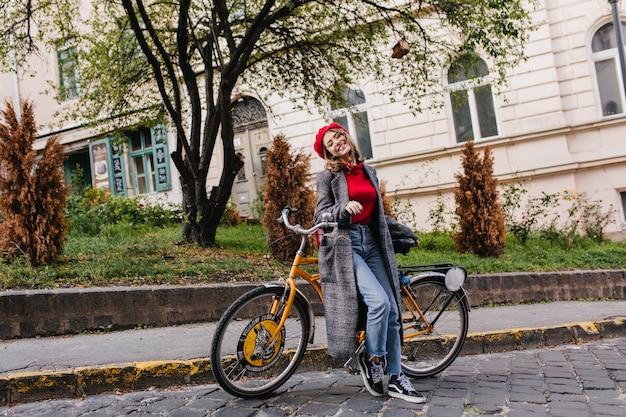 Het portret van gemiddelde lengte van modieuze vrouwelijke student in uitstekende jeans die met gele fiets stellen