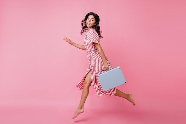 Het portret van gemiddelde lengte van mooie vrouw in sprong. dame in gestreepte outfit gaat snel met bagage.