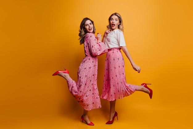 Het portret van gemiddelde lengte van twee vriendinnen draagt rode schoenen met hoge hakken. binnenfoto van enthousiaste dames die samen chillen.