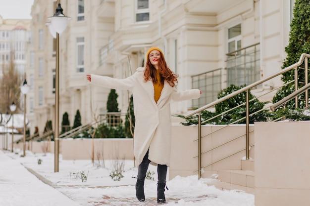 Het portret van gemiddelde lengte van vrolijke kaukasische vrouw die op sneeuwstraat glimlacht. vrolijk gembermeisje dat pret heeft in koude dag.