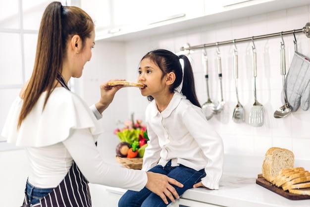 Het portret van geniet van gelukkige liefde aziatische familiemoeder en weinig aziatisch meisjeskind glimlachend en voorbereiding van het koken van ontbijt samen in de keuken thuis