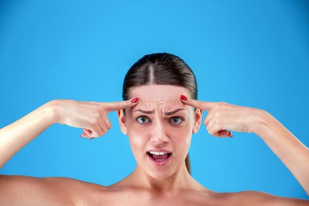 Het portret van geschokte jonge vrouw bekijkt teleurgesteld camera met terwijl het aanraken van haar rimpels op voorhoofd op blauwe achtergrond