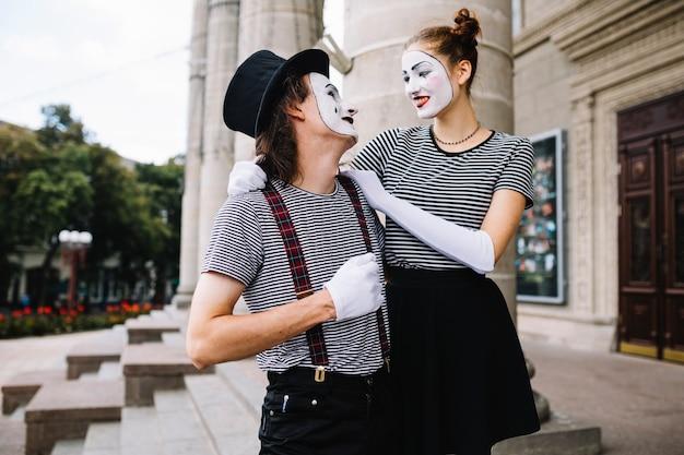 Het portret van glimlachen bootst paar wijzend na die elkaar bekijken