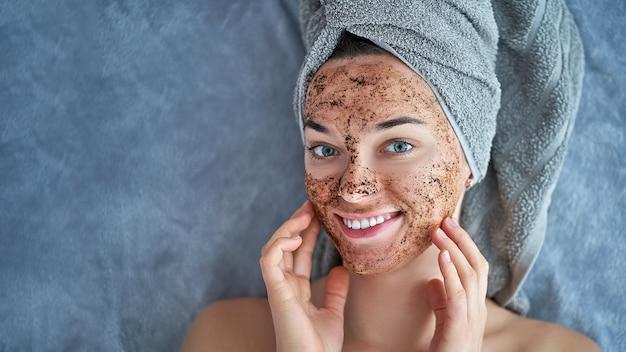 Het portret van glimlachend gezond wijfje in badhanddoek met natuurlijke reinigende gezichtskoffie schrobt na douche